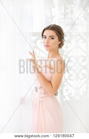 Beautiful young bride with wedding makeup and hairstyle in bedroom, newlywed woman final preparation for wedding. Happy Bride waiting groom. Marriage Wedding day moment.