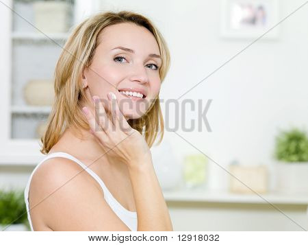 Beautiful Smiling Girl Applying  Cream On Face