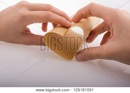 Paper forming a heart shape in hand on a white background