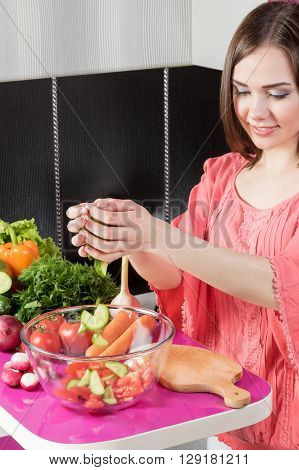 Young woman in the kitchen adding sliced cucumber in a bowl with salad