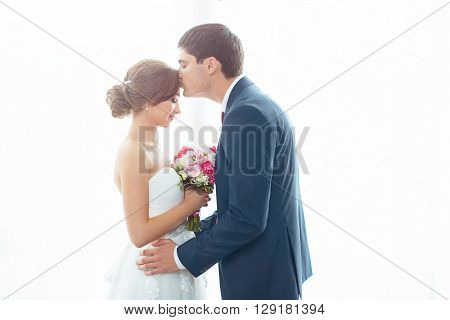 Wedding couple in love. Beautiful bride in white dress with brides bouquet and handsome groom in blue suit standing and embracing each other indoors at home, white bright isolated background. Husband kissing his wife