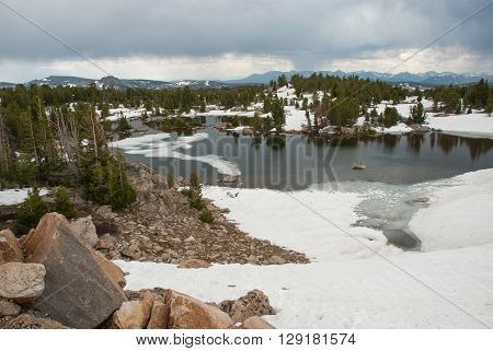 Ice and snow on the shores of alpine lake at summer day Beartooth Pass Wyoming USA
