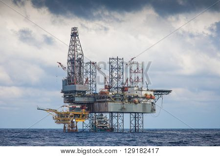 Oil and gas drilling rig working on remote wellhead platform to drill the oil and gas reservoir