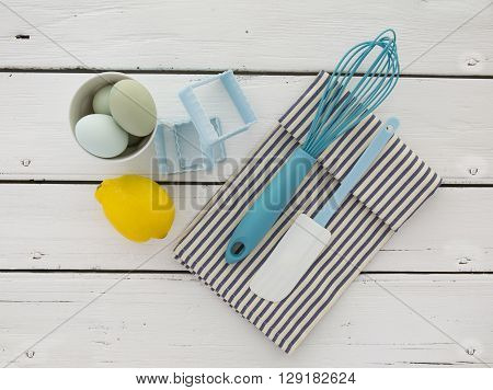 Eggs in a ceramic bowl with a whisk and lemon on a rustic white painted wood table top shot from above