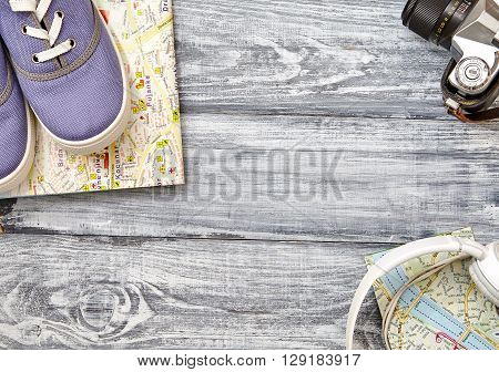 Vacation and travel items. Travel concept - headphones camera shoes map on a wooden background