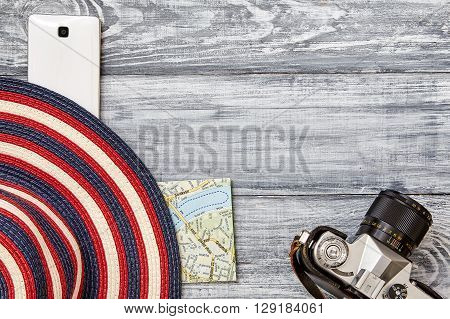 Vacation and travel items. Travel concept. Camera map hat telephone on a wooden background