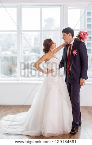 Wedding couple in love. Beautiful bride in white dress with brides bouquet and handsome groom in blue suit standing and embracing each other indoors in decorated studio room, white bright interior with big window.