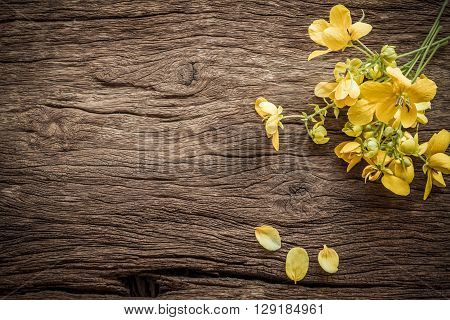 Summer flowers on a wooden old background. Beautiful flower background with yellow flowers in vintage style.