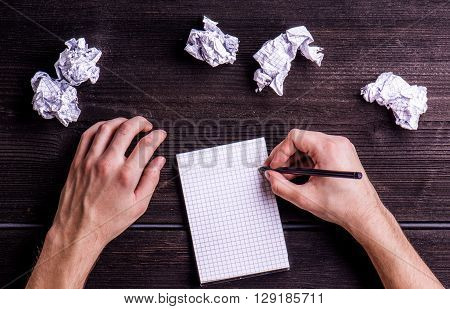 Hands of unrecognizable man writing on squared piece of paper, crumpled paper balls. Flat lay. Workplace. Studio shot on dark wooden background.