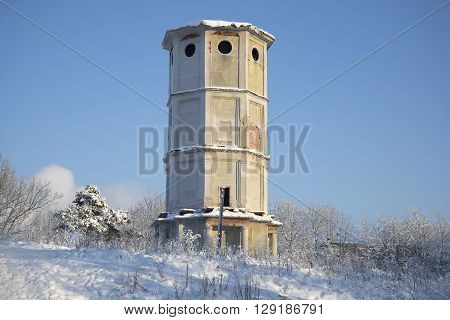 Old water tower in winter landscape. Gatchina, Russia