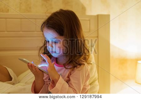 Cute little girl with smartphone lying in a bed, bedtime
