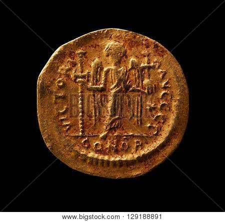 Ancient golden coin with angel closeup macro shot