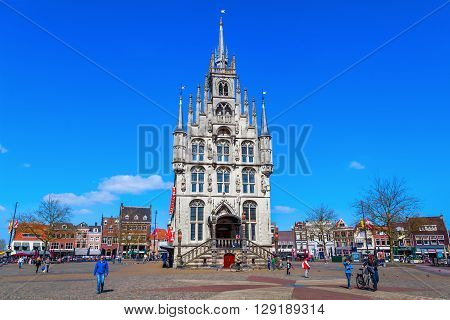 Gouda Netherlands - April 20 2016: old city hall of Gouda with unidentified people. It was built between 1448 and 1450 and is one of the oldest Gothic city halls in the Netherlands