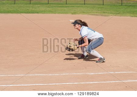 Female softball player crouched and ready for the ball on defense.