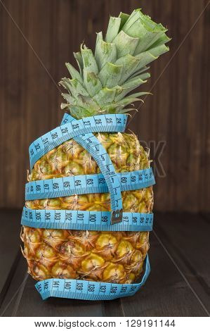 Fresh pineapple with measuring tape on the wooden table. Diet food.