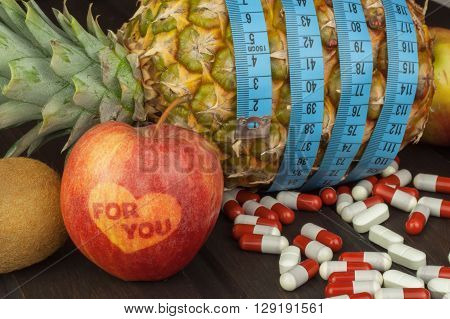 Fresh pineapple and apple with measuring tape on the wooden table. Dietary supplements.
