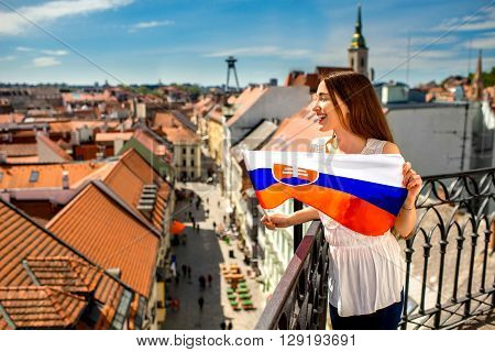Young female tourist holding slovak flag in Bratislava city. Promoting tourism in Slovakia