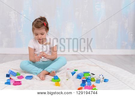Child girl playing with toys and builds constructor. Blank space for text