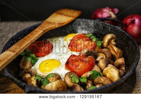 Fried eggs with mushrooms tomatoes and herbs in the old cast iron skillet