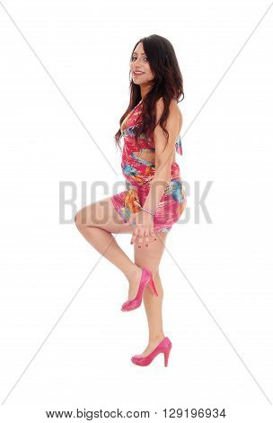 A pretty East Indian woman in a colorful dress lifting up one leg standing in profile in high heels isolated for white background.