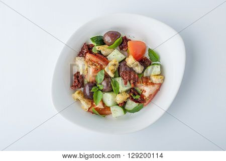 Panzanella salad with sun-dried tomatoes and ciabatta in a ceramic plate horizontal