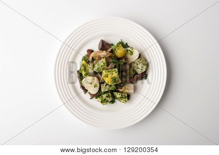 Salad with porcini mushrooms in a ceramic plate on a white background horizontal