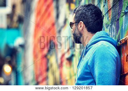 Profile of a stylish handsome guy wearing sunglasses and casual clothing standing near beautiful colorful city wall background, looking away, urban lifestyle