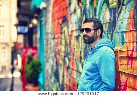 Handsome man wearing stylish sunglasses, standing near beautiful colorful wall on the street, fashion urban look, city life