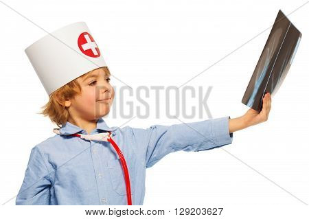 Young 5 years old doctor with stethoscope studying an x-ray of hand, isolated on white