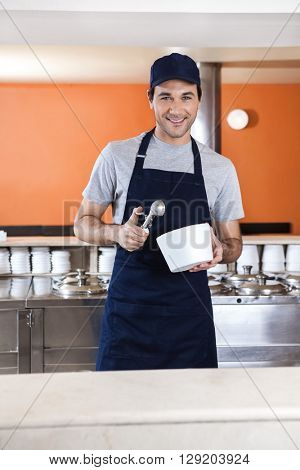 Smiling Waiter Holding Scoop And Bowl In Ice Cream Parlor