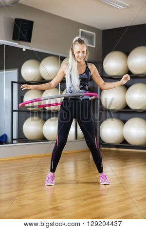 Happy Woman Exercising With Hula Hoop In Gym