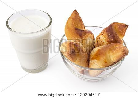 Fresh Serbian pastry rolls with cheese and sesame, in the glass bowl with glass of yogurt, kifla kiflice, isolated on white background