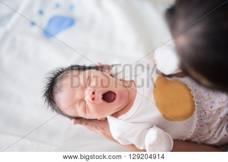 Cute asian baby newborn looking at grandmom yawning
