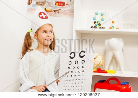 Beautiful girl playing oculist, pointing to the testing card at medical office