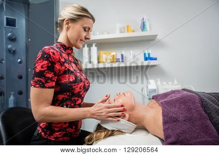Beautician Giving Facial Massage To Woman In Beauty Parlor