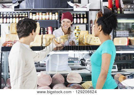 Saleswoman Selling Cheese To Couple In Grocery Store
