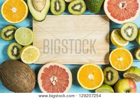 citrus fruits in the center of a wooden board on a blue table top view