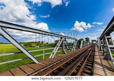 Old railroad bridge profiled on blue sky in summer