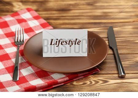 Brown plate on a brown wooden table, lifestyle