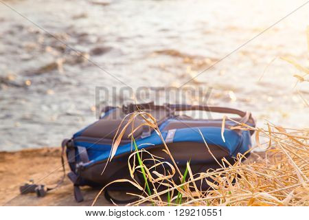 The backpack lies on a stone against water flow. The dry grass in the foreground a backpack of blue color a scene is lit with the sunset sun