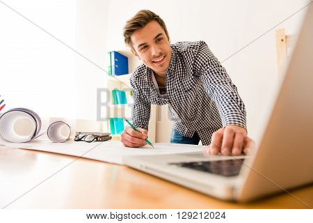 Cheerful Young Man Using Laptop To Create His Scheme
