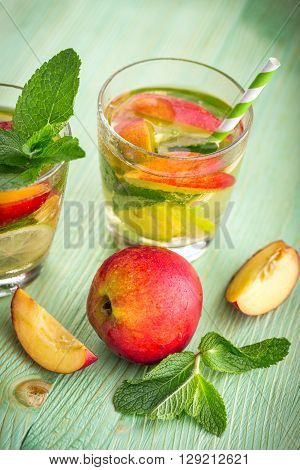 Cold fresh lemonade drink with nectarine lime and mint on a green wooden background