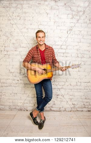 Smiling Man Standing Near The Wall And Playing On The Guitar