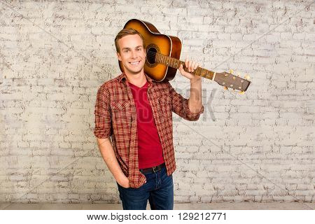 Young Pretty Man Standing With Guitar Near The Brick Wall