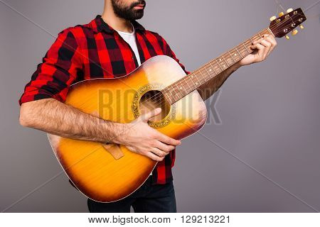 Close Up Portrait Of Young Bearded Man Holding Guitar