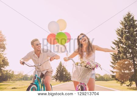 Portrait Of Heerful Young Woman And Her Boyfriend Having Walk With Bicycles