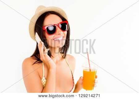 Happy Woman In Spectacles And Summer Hat Drinking Juice And Talking On Phone