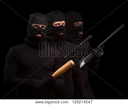 Picture of dangerous gangsters in balaclavas over black background. Men in black masks posing with bat, rifle and gun in studio. Isolated on black.