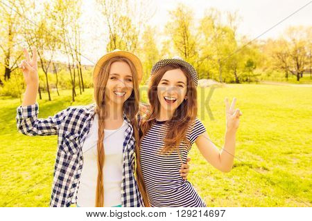 Two Attractive Sisters In Hats Having Fun And Gesturing With Two Fingers
