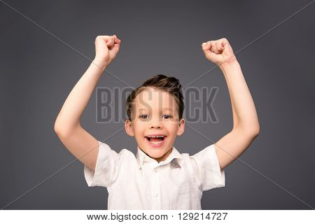 Portrait Of Happy Little Boy Triumphing With Raised Hands